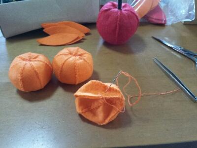 オレンジのフェルト7枚を、みかんの形に縫い合わせ、